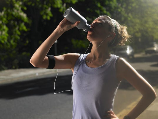 Young woman standing at street, drinking after jogging