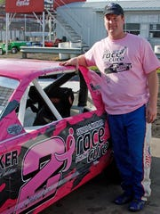 Kevin Sharp poses for a photo with his No. 2 car that's