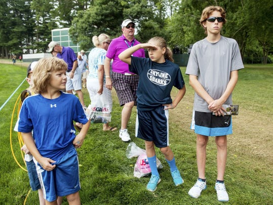 Ella Sheaffer, 11, of Lancaster, watches players walk down the fairway of the 10th hole with brothers Gabriel, 7, and Peyton, 13, on Wednesday during the final practice round of the 70th U.S. Women's Open at Lancaster Country Club.