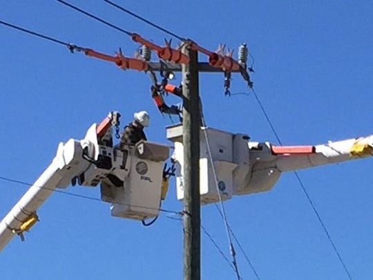 FPL workers reconnect power lines over Summerlin Road.