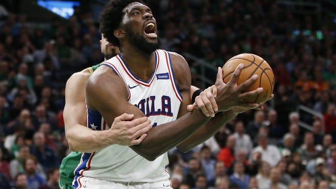 Philadelphia 76ers center Joel Embiid (21) is fouled by Boston Celtics center Enes Kanter (11) during the second half at TD Garden.