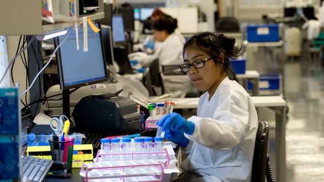 Melina Gomez, an employee of NeoGenomics, signs in specimens in October 2014. The company released earnings Tuesday.