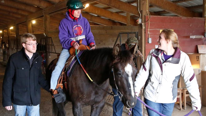 Mikel Livingston, left, Anna McCulfor and Jake Rhoda walk with Peg Carson, who receives Therapeion's horse-riding therapy.