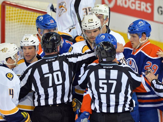 Referees separate Edmonton Oilers left wing David Perron (57) and Nashville Predators center Paul Gaustad (28) after a stop in play at Rexall Place.