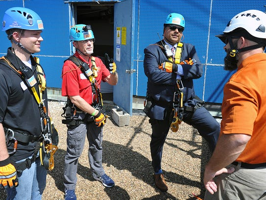 Rappelling instructor Troy Wilson, right, talks with