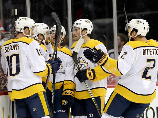 Nashville Predators players celebrate a goal by defenseman Yannick Weber, second from left, of Switzerland, during the first period of a game against the New Jersey Devils on Thursday.