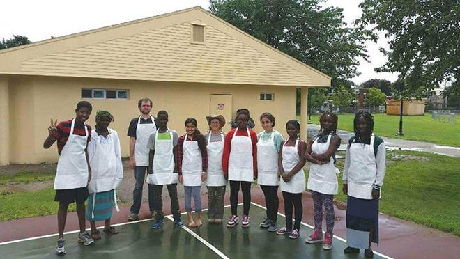 Group of muralists pose with their clean aprons before the painting project.