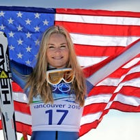 Lindsey Vonn, the 2010 Female Athlete of the Year, holds the Stars and Stripes during the flower ceremony for the Women's super-G at the Vancouver 2010 Olympics in Whistler, British Columbia.