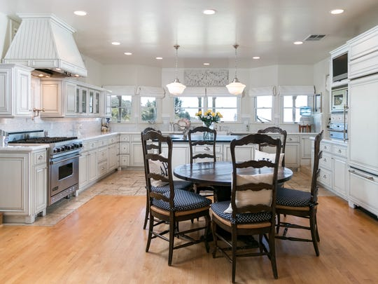 The kitchen is wide open and inviting, with recessed lighting and multiple windows providing lots of illumination.