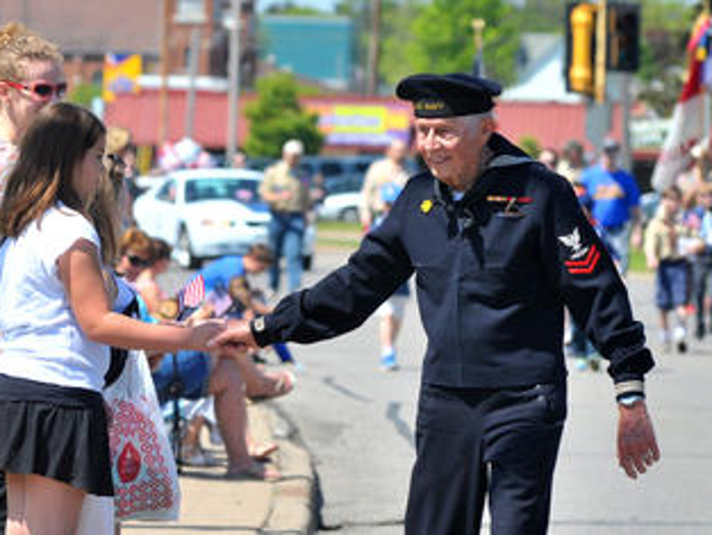 A young lady receives a handshake from a retired war