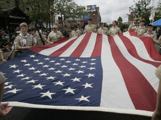 Boy Scout Troop 18, based in Freehold, carries a large American flag along Main Street in Freehold Borough during the town's 142nd Memorial Day Parade last year.