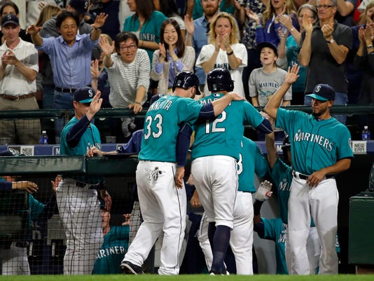 Fans cheer as Seattle Mariners' Chris Iannetta (33) and Leonys Martin (12) are greeted at the dugout by Luis Sardinas, right, after Iannetta and Martin scored on a three-run triple by Ketel Marte during the sixth inning of a baseball game against the Los Angeles Angels, Friday, May 13, 2016, in Seattle. (AP Photo/Ted S. Warren)