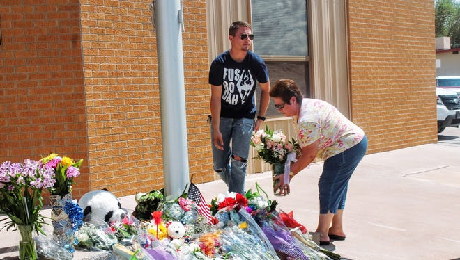 Residents place flowers at a makeshift memorial in front of the Alamogordo Police Station, 700 Virginia Ave.
