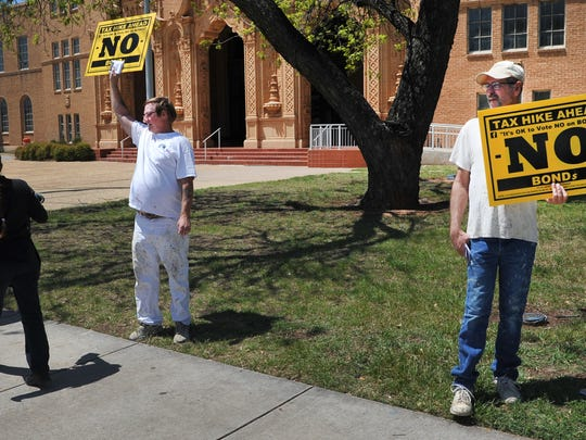 Roy Stancliff, left, and Marshall Reed stand outside of Memorial Auditorium, an early voting location, with signs in protest of a possible tax increase if a proposed bond is passed by Wichita Falls voters.