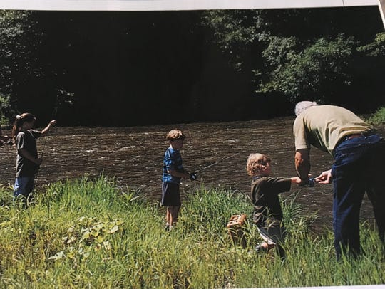 Josey Jewell gets some help fishing from his grandfather,