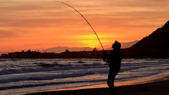 The sun sets behind a fisherman at the Oil Piers.