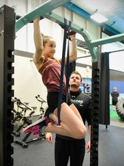 Madelyn Anderson, 11, does pull-ups as trainer Isaiah McBride, director of HARDcore Elite Sports Performance at Rejuv, watches Wednesday, Nov. 15, at Rejuv in Waite Park.