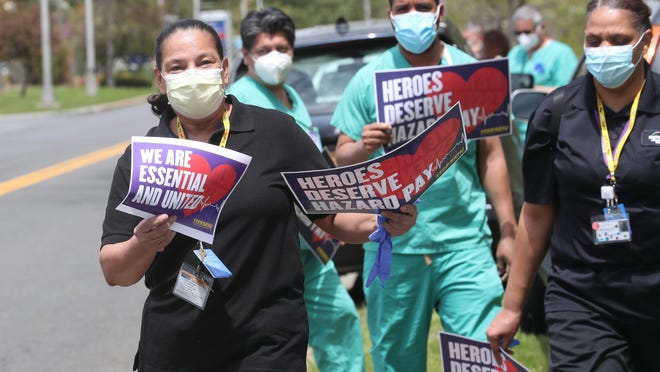 Westchester Medical Center workers hold a silent vigil outside the medical center in Valhalla May 14, 2020.The workers are still looking for any form of hazard pay for their work during the unprecedented COVID-19 pandemic.