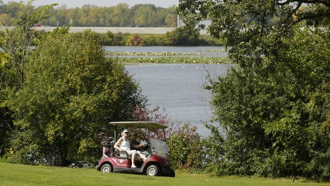 Golfers ride in a cart Sept. 15, 2017, at Lakeshore Municipal Golf Course in Oshkosh.
