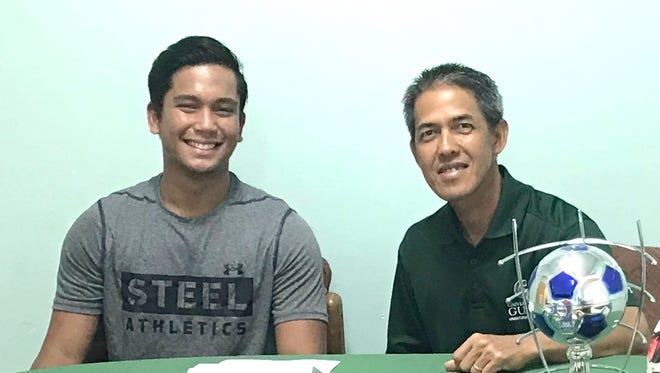 Jake Cameron Delfin Uncangco shakes hands with Rod Hidalgo, the University of Guam's men's soccer coach after signing a letter of intent.