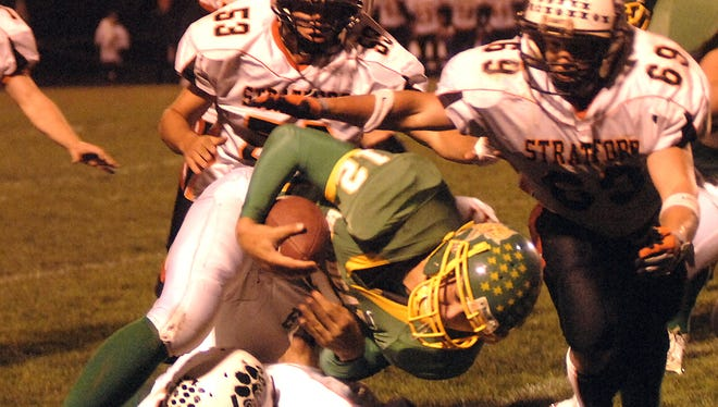 Edgar quarterback Justin Sinz is brought down by a trio of Stratford defenders in a 2008 regular season game. The two programs met for the WIAA Division 6 state championship that year, one of the seasons recapped by a Two Rivers author's book which chronicles the rivalry and success of the programs.
