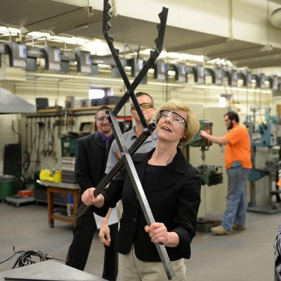 Sen. Tammy Baldwin, left, talks about manufacturing technology with instructor Andy Belongia during a tour of the Bay Link Manufacturing lab at West High School April 1, 2015.