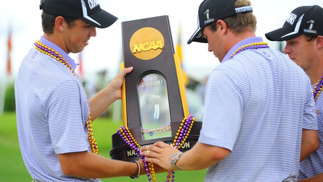 Former Loyola College Prep star Eric Ricard (left) eyes LSU's national championship trophy in 2015.