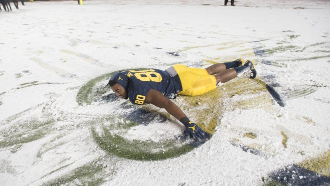 Michigan fullback Khalid Hill makes snow angels on the turf at the end of the game.