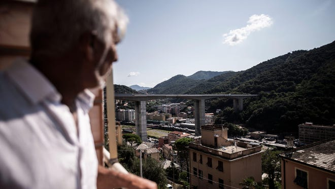 A man looks from his balcony towards the E80 highway bridge of Staglieno in Genoa on August 17, 2018, which is one of the largest in Genoa.