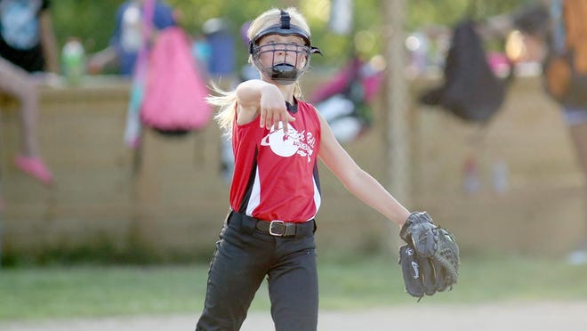 Rick Ball pitcher Brooklyn Alberts throws to first to record the out in Babe Ruth 10U softball Friday night at Lions park. River Rats won both games against Rick Ball 8-3 and 9-2.