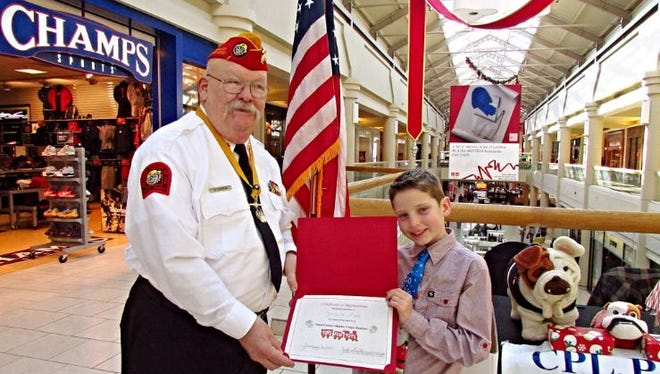 Liam Tomasulo Gillespie receives an award from Bob Kubinack, Chairman of the Cpl Phillip A. Reynolds detachment of the Marine Corps League in Freehold.