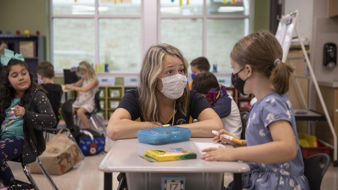 Fourth grader Charlie Stanton, 9, practices a social distancing technique on the first day of in-person classes Tuesday at Rough Hollow Elementary School in the Lake Travis district.