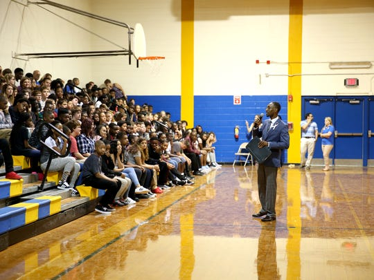 Augustus Raa Middle School Principal Christopher Small speaks to eight-graders in the gymnasium at a first day of school assembly Monday.