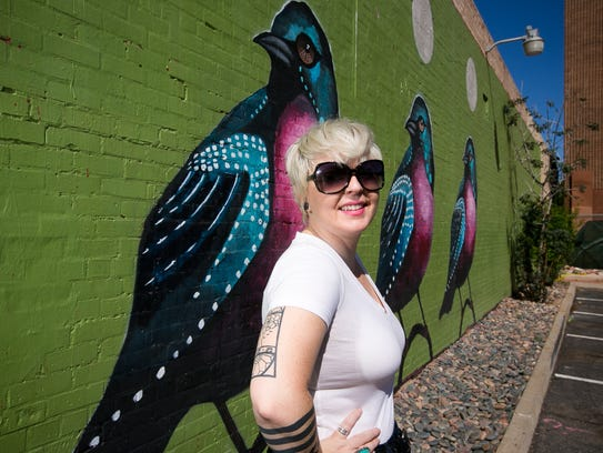 "Lauren Lee stands in front of her mural ""Three Birds"""