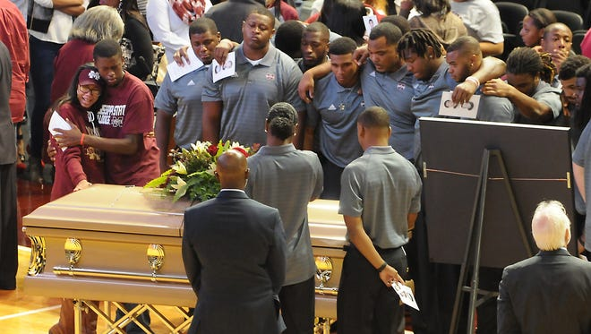 Mississippi State team members surround the casket of Keith Joseph Jr. after a memorial service on Nov. 13. Two freshmen, Jamal Peters and Mark McLaurin, were close to Joseph and continue to mourn his loss.