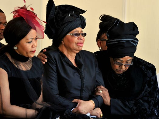 Nelson Mandela's ex-wife, Winnie Mandela, right, comforts the widow of Mandela, Graca Machel, center, during the burial.
