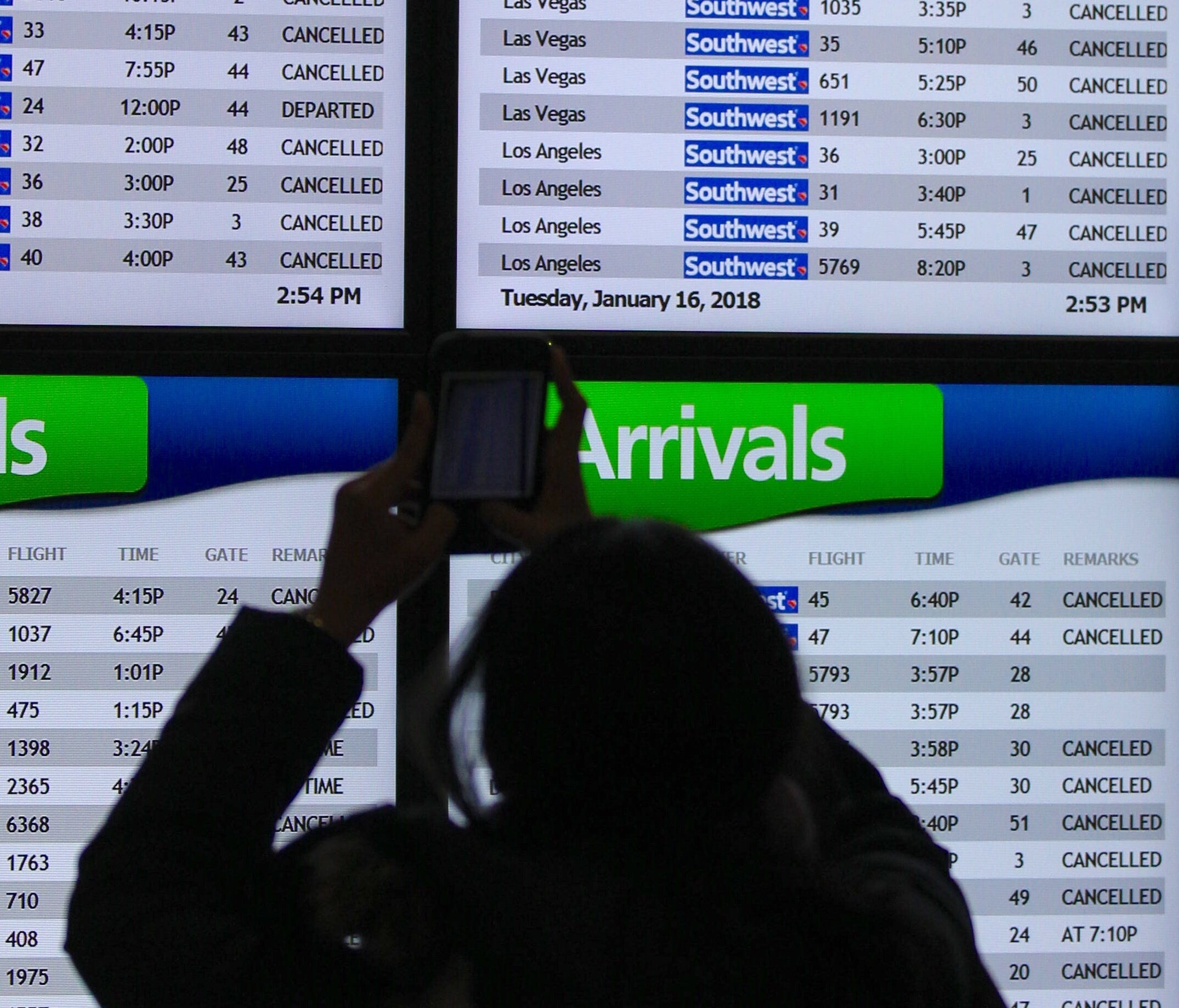 A passenger takes a picture of a flight departure screen that shows mostly canceled flights at Houston Hobby Airport on Tuesday, Jan. 16, 2018. The city was hit by wintry weather.