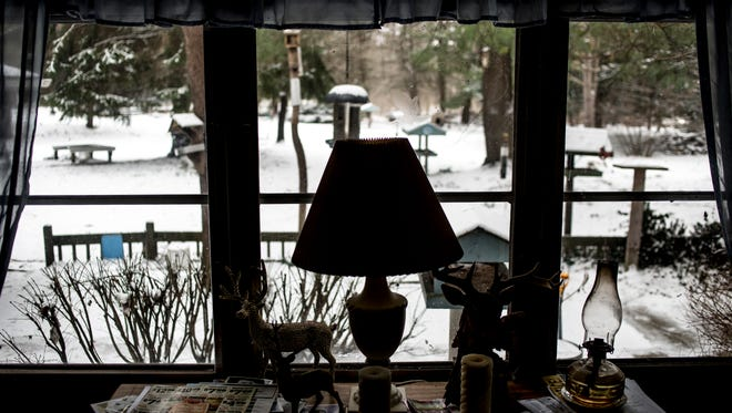 An electric lamp is seen among an oil lamp and candles at Bob Putze's home in Clyde Township.