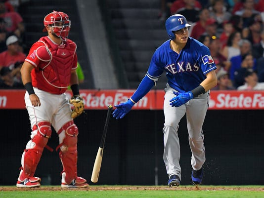 Texas Rangers' Drew Robinson, right, drops his bat after hitting a two-run home run, next to Los Angeles Angels catcher Juan Graterol during the third inning of a baseball game, Thursday, Aug. 24, 2017, in Anaheim, Calif. (AP Photo/Mark J. Terrill)