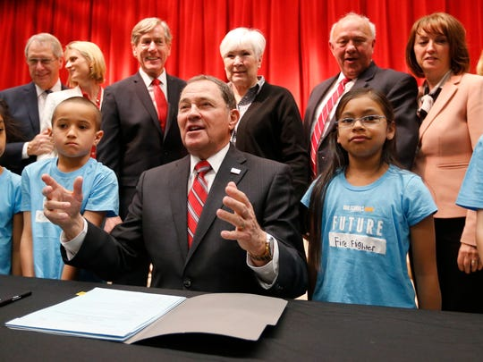 Utah Gov. Gary Herbert, center, is surrounded by students from the Meadowbrook Elementary School during a bill signing ceremony at the Meadowbrook Elementary School Monday, April 16, 2018, in Bountiful, Utah. Herbert signed the bill creating a path to raise education funding in a deal lawmakers reached with a well-connected group of business, political and education leaders. (AP Photo/Rick Bowmer)
