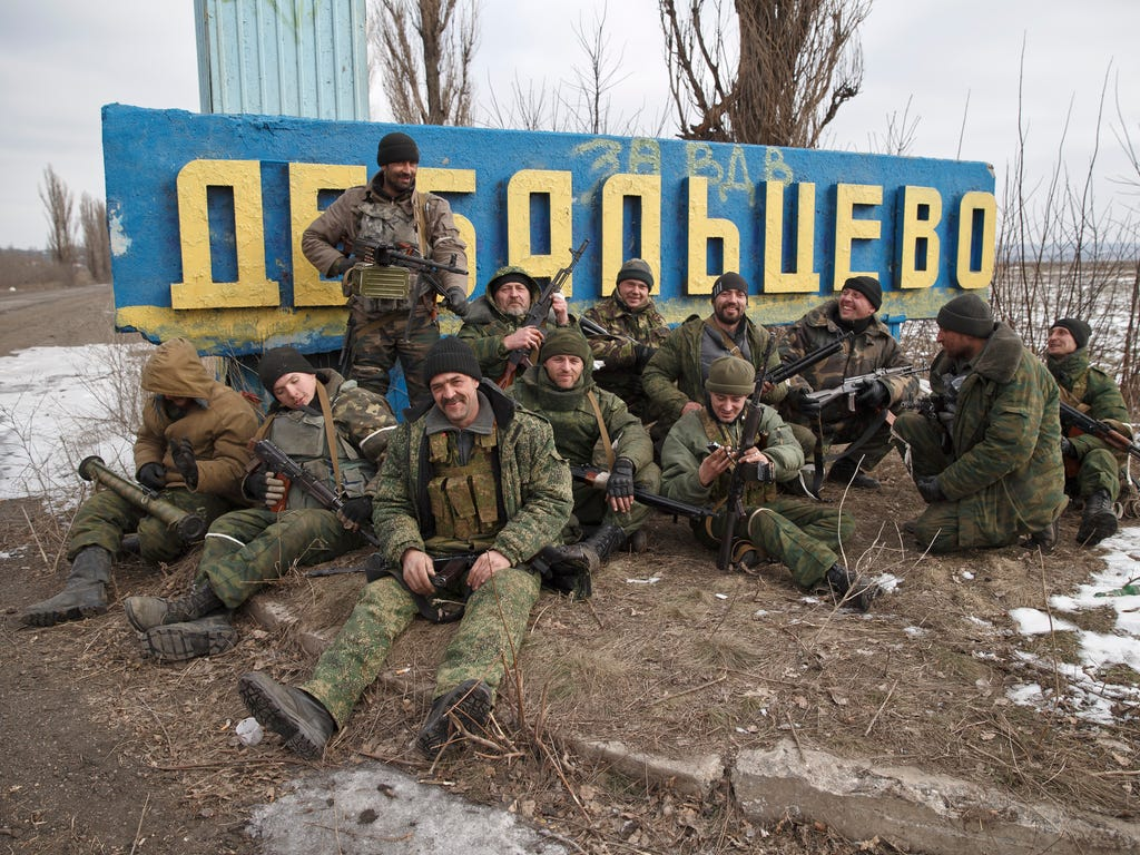 Russia-backed rebels pose by a road sign on Feb. 20, 2015, at the entrance in Debaltseve, Ukraine, after checking the access road into town for mines they suspected were laid down by retreating Ukrainian government troops. After weeks of relentless f