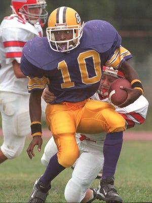 East High's Reggie Cox runs for yardage.