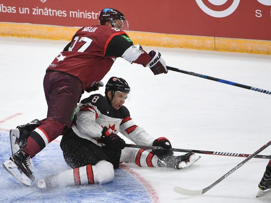 FILE - In this Feb. 4, 2018 file photo, Latvia's Gints Meija, left, and Canada's Wojtek Wolski fight for the puck during an exhibition hockey game in Riga, Latvia. Wolski is playing for Canada at the 2018 Winter Olympics just 16 months after breaking his neck from crashing head-first into the boards. (AP Photo/Roman Koksarov, File)
