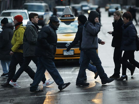 Pedestrians cross a street on Broadway at one of the deadliest intersections in Manhattan.