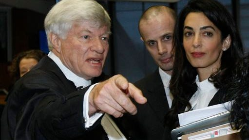 Geoffrey Robertson, left, a member of a legal team representing Armenia, shows the way to his colleague Amal Clooney, right, as they enter the European Court of Human rights in Strasbourg, eastern France, Wednesday. Clooney, the wife of George Clooney, is among the lawyers arguing at the European Court of Human Rights against a Turkish man convicted in Switzerland for denying the 1915 Armenian genocide. Armenia, which argues that denying the genocide should be a crime as denying the Holocaust is in many European countries, is challenging a decision that ruled the man's right to free expression was violated.