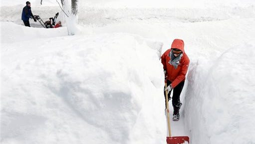 Kim Taylor of Norwood, Mass., is surrounded by snow as she shovels a path in front of her home Sunday, Feb. 15, 2015, in Norwood. A storm brought a new round of wind-whipped snow to New England on Sunday,  forcing people to contend with a fourth winter onslaught in less than a month.