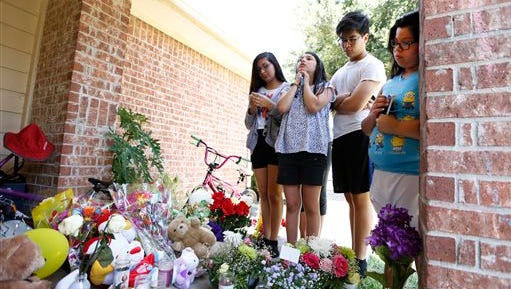 """From left, Wendy Antonio, Valerie Perdomo, Carlos Sanchez and Jessica Sanchez brought flowers and offered prayer at a memorial outside of the home of Valerie Jackson, where 6 children and two adults were murdered Saturday night. """"I don't want to cry anymore"""" Antonio said as Perdomo offered a prayer Monday, Aug. 10, 2015, in Houston. (Steve Gonzales/Houston Chronicle via AP) MANDATORY CREDIT"""