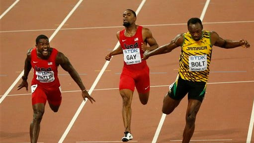 United States' silver medal winner Justin Gatlin, United States' Tyson Gay and Jamaica's gold medal winner Usain Bolt, from left, cross the line in the men's 100m final during the World Athletics Championships at the Bird's Nest stadium in Beijing, Sunday, Aug. 23, 2015. (AP Photo/Mark Schiefelbein)