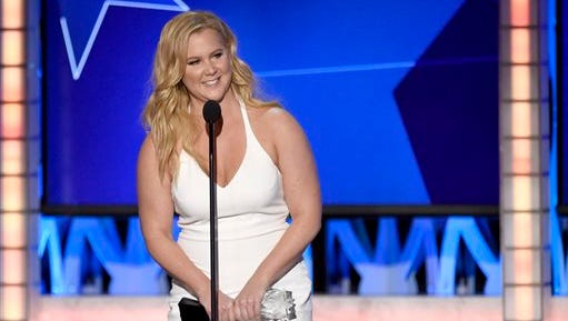 """Amy Schumer accepts the award for best actress in a comedy for """"Trainwreck"""" at the 21st annual Critics' Choice Awards at the Barker Hangar on Sunday, Jan. 17, 2016, in Santa Monica, Calif. (Photo by Chris Pizzello/Invision/AP)"""
