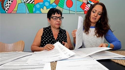 Ana Granado, left, and her daughter Andreia Walker, right, look over healthcare paperwork at their home in Charlotte, N.C., on Wednesday. Granado had health insurance through the federal health care law and was undergoing treatment for breast cancer when she found out her premiums were going up more than six-fold. She's among hundreds of thousands of people whose coverage is jeopardized annually by paperwork problems. Hundreds of thousands of people lose subsidies under the health law, or even their policies, when they get tangled in a web of paperwork problems involving income, citizenship and taxes.